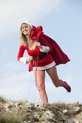 Female Santa running with sack of presents