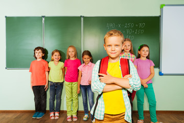 Smiling boy stands in front near blackboard