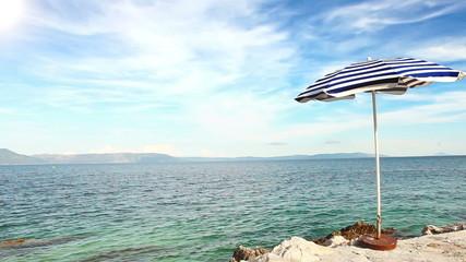 Alone beach retro style umbrella on the croatian shore