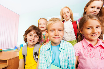 Kids sit near desk and smile in classroom