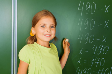 Cute girl with chalk in hand near blackboard