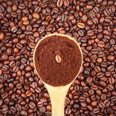 Cucchiaio di caffè macinato e chicchi sullo sfondo
