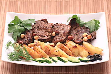 grilled meat on a plate served with vegetables