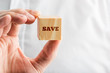 Man holding a wooden cube saying - Save