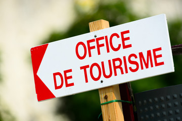 Tourism office streetsign on wooden pole pointing towards left