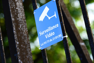 Blue sign of video surveillance fastened to metallic fence