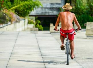 Topless man cycling on a bike