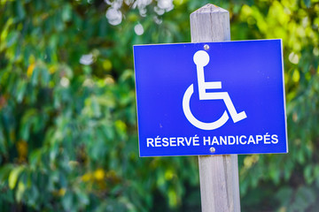 Wheelchair handicap sign fastened on a wooden pole