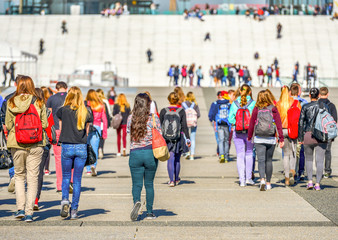 A lot of colorful beautiful youngsters walking towards stairs to