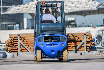 A construction worker driving a blue construction machine