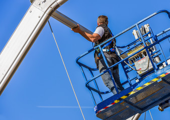 Construction worker fastening roof ridge on skylift