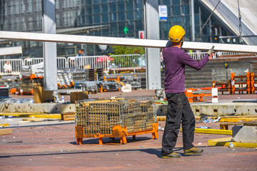 A construction worker in purple blouse and yellow helmet