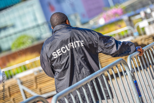 Security worker leaning over metallic fence - 71017319