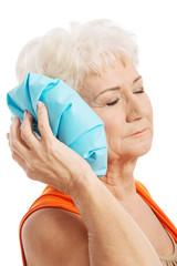An old elegant lady is having a headache