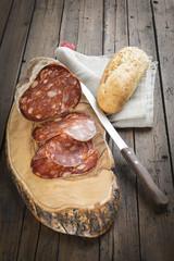 Morcón ibérico en lonchas y barra de pan sobre la tabla de corte