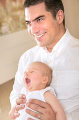 Happy father with yawning daughter on hands
