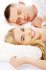 Young adult couple sleeping on the bed