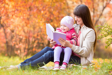 mother reading a book to kid outdoors in fall