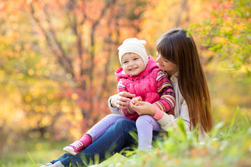 beautiful young mother and her daughter have fun sitting at autu