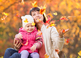 Kid and beautiful mother play and throw leaves outdoor in autumn