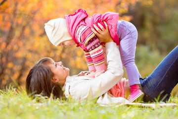 happy mother and kid girl play outdoors in fall