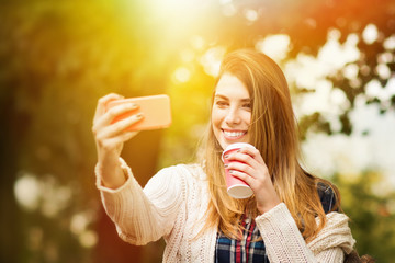 Beautiful blonde woman with takeaway coffee taking a selfie
