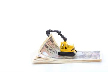 お金とショベルカー