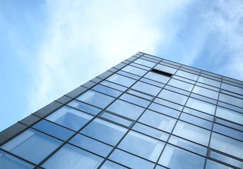 Modern office building wall made of glass and steel with blue sk