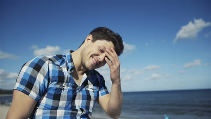 Handsome man in checkered shirt over bright beach background