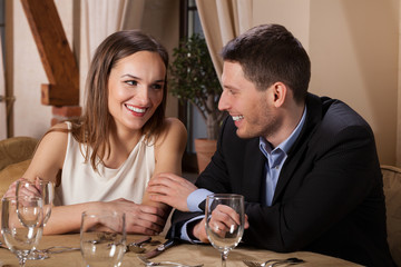 Smiling couple waiting for dinner in restaurant