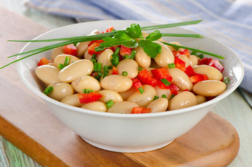 White bean salad   on a wooden board.
