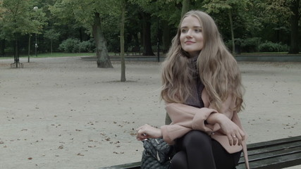 Cheerful woman waiting for someone on a bench in autumnal park.