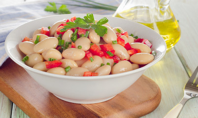 White bean salad   on a wooden table.