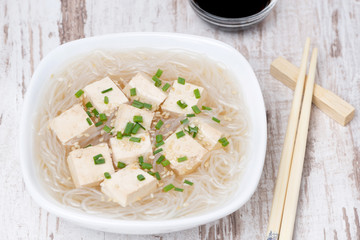 soup with rice noodles, tofu and green onions, top view