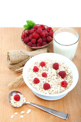 Fresh raspberries, Oatmeal flakes and milk on a wooden table.