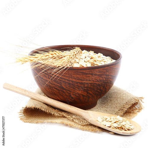 canvas print picture Oatmeal flakes in wooden bowl. Healthy food.