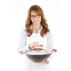 Portrait of housewife holding pan against white background.