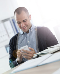 Smiling office worker using smartphone at work