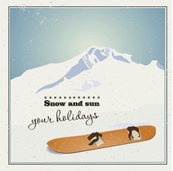 Winter  background. Mountains and old snowboard in the snow