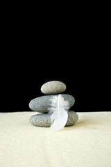 Three stones with white feather on sand with black background