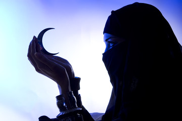 Beautiful young muslim girl holding a moon symbol, spirituality,