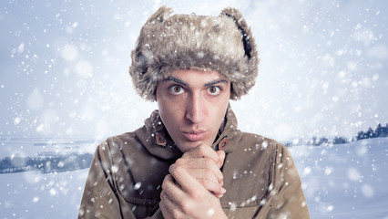 Portrait of young man with eskimo hat and winter  background wit