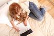 Blondes Mädchen im Bett mit Laptop