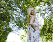 happy blond young woman in park smiling