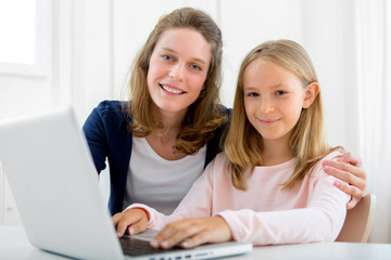 Attractive woman and little sister using laptop