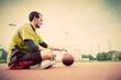 Young man on basketball court. Sitting and dribbling with ball