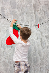 Boy hangs socks for Santa Claus.