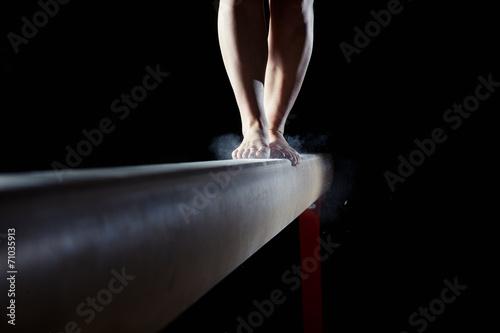 Tuinposter Gymnastiek feet of gymnast on balance beam