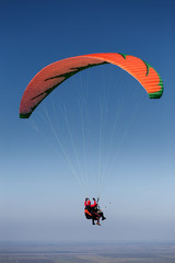 Two paragliders in flight above the land
