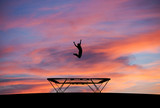 Fototapety silhouetted man jumping on trampoline in sunset